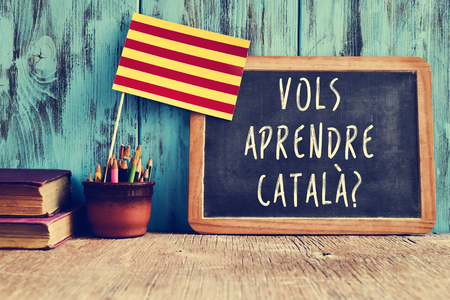 lomography: a flag of Catalonia and a chalkboard with the question vols aprendre catala?, do you want to learn Catalan? written in Catalan in it Stock Photo