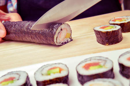 japanese cookery: closeup of a young man preparing makizushi, filled with avocado and shrimps