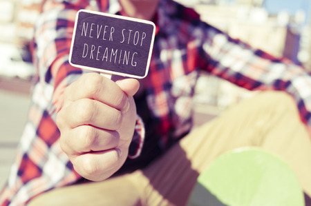 counsel: closeup of a young skater man showing a signboard with the text never stop dreaming
