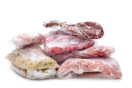 freezer: frozen raw meat, such as pork, chicken or beef, wrapped in plastic on a white background