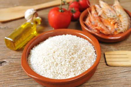 kitchen spanish: some ingredients to prepare a spanish paella or arroz negro, such as rice, tomato, garlic or shrimps, on a rustic wooden table