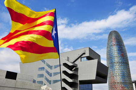 separatist: Barcelona, Spain - September 11, 2015: A pro-independence flag with the Agbar Tower in the background in Barcelona, Spain, during the rally in support for the independence of Catalonia