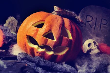 dismal: closeup of a Halloween jack-o-lantern in a dismal scenery, with skulls and gravestones Stock Photo