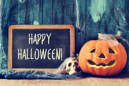 spiders, cobwebs, a skull, a jack-o-lantern and a chalkboard with the text happy halloween written in it Stock Photo