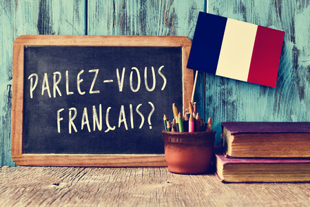blue you: a chalkboard with the question parlez-vous francais? do you speak french? written in french, a pot with pencils and the flag of France, on a wooden desk