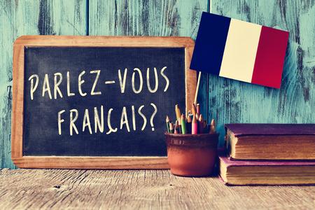 una pizarra con la pregunta Parlez-vous francais? ¿Habla usted francés? escrito en francés, una olla con los lápices y la bandera de Francia, en un escritorio de madera Foto de archivo