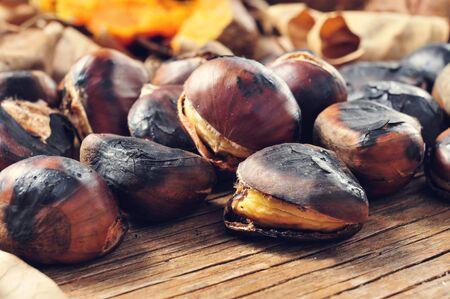 castaÑas: primer plano de unas castañas asadas sobre una mesa de madera rústica con algunas batatas asadas y hojas de otoño en el fondo Foto de archivo