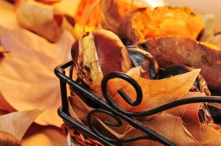 tots: closeup of a rustic basket with some roasted chestnuts, some roasted sweet potatoes and autumn leaves