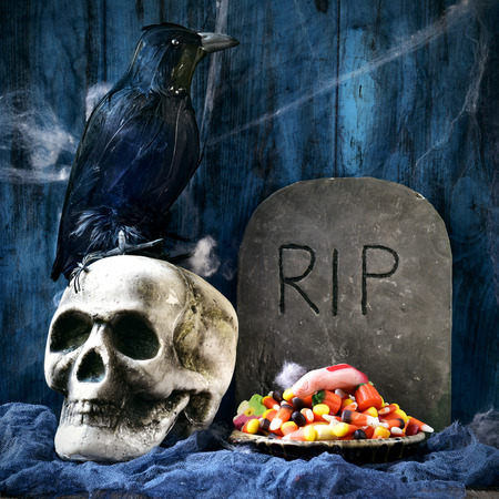 dismal: a plate with Halloween candies and an amputated finger in a dismal scene with a crow, a skull and a gravestone with the text RIP carved in Stock Photo