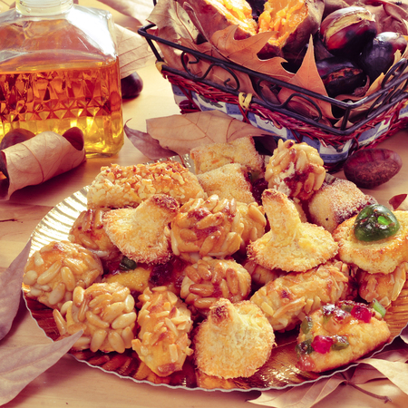 tots: closeup of a plate with panellets, some roasted chestnuts and sweet potatoes in a basket, and sweet wine in a glass bottle, typical snack in All Saints Day in Catalonia, Spain