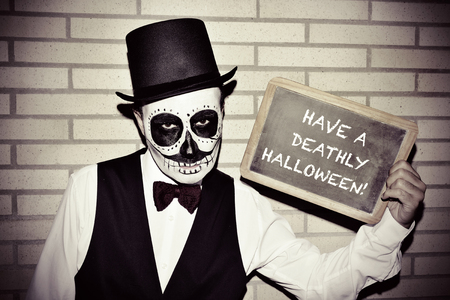 a man with calaveras makeup, wearing bow tie and top hat, against a brick wall, shows a chalkboard with text have a deathly halloween written in it Stock Photo