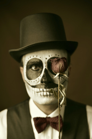 portrait of a young man with calaveras makeup, wearing bow tie and top hat, with a dry rose in front of his eye, with a vintage effect