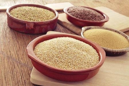 brown flax: some earthenware bowls with amaranth, quinoa, brown flax and buckwheat seeds on a rustic wooden table