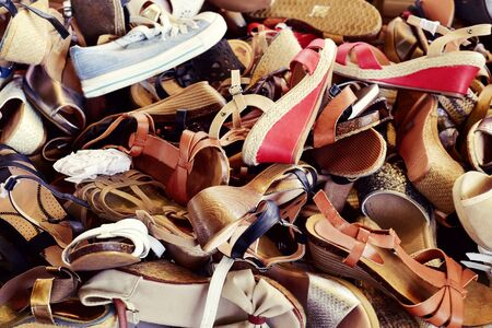 footgear: closeup of a pile of different woman shoes on sale in a street market