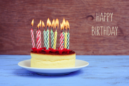 yesteryear: the text happy birthday and a cheesecake with some lighted birthday candles of different colors, on a rustic blue wooden table