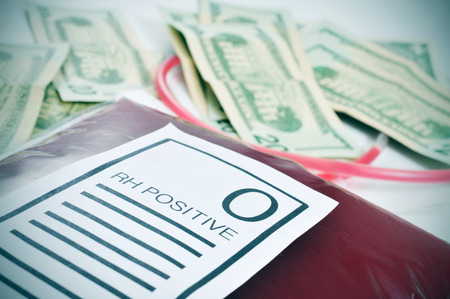 paid medicine: closeup of a blood bag with a label with the text O RH positive and a pile of US dollar bills in the background