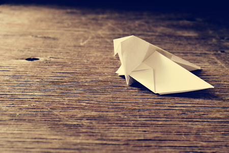 origami bird: an origami bird on a rustic wooden surface, with a retro effect