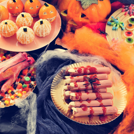 amputated: some plates with different Halloween food, such as candies, scary fingers or mandarines as pumpkins, with different scary ornaments as an amputated hand, spiders and cobwebs Stock Photo