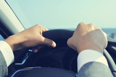 valeting: closeup of a young man wearing a gray suit driving a car, with a filter effect