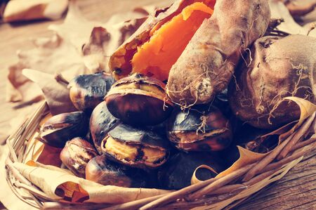 tots: some roasted chestnuts and some roasted sweet potatoes in a wicker basket with autumn leaves, on a rustic wooden table