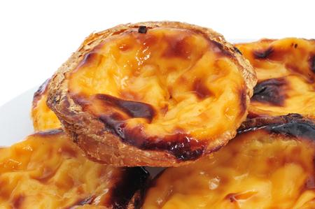 sweet background: some pasteis de nata, typical Portuguese egg tart pastries, on a white background