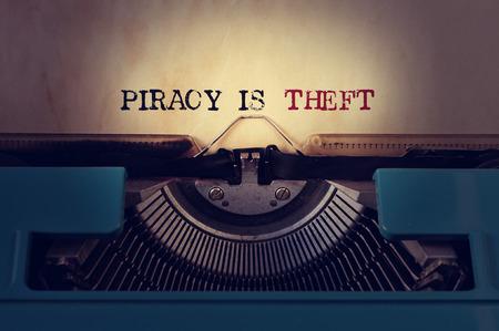 maquina de escribir: primer plano de una máquina de escribir retro azul y la piratería texto está escrito con el robo en una lámina de color amarillento Foto de archivo