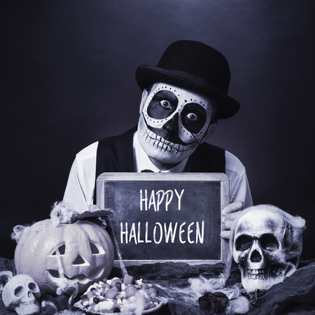 dismal: a man with calaveras makeup, wearing bowler hat, shows a chalkboard with the text happy halloween, in a dismal scene with a carved pumpkin and skulls, in black and white Stock Photo