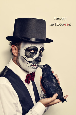 a man with calaveras makeup, wearing bow tie and top hat, with a black crow in his hand, and the text happy halloween Stock Photo