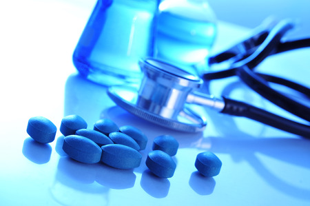 auscultate: closeup of the desk of a doctors office with pills a stethoscope and some flasks