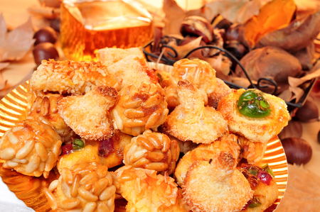 all saints day: closeup of a plate with panellets, some roasted chestnuts and sweet potatoes in a basket, and sweet wine in a glass bottle, typical snack in All Saints Day in Catalonia, Spain