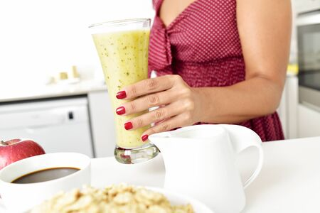 sexy housewife: closeup of a young woman in a red dress with a glass with a smoothie in his hand, and a cup of coffee, a bowl with oatmeal cereal and a red apple on the kitchen table Stock Photo