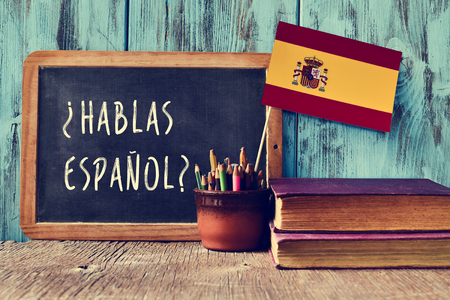 spanish flag: a chalkboard with the question hablas espanol? do you speak Spanish? written in Spanish, a pot with pencils and the flag of Spain, on a wooden desk