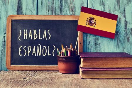 Eine Tafel mit der Frage hablas espanol? Sprechen Sie Spanisch? in Spanisch, einen Topf mit Stiften und der Flagge Spaniens geschrieben, auf einem hölzernen Schreibtisch