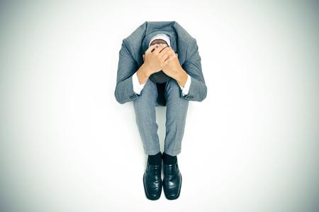 ansiedad: un hombre de negocios acurrucada en el suelo con la cabeza entre las rodillas y las manos en la cabeza, ilustración leve añadió Foto de archivo