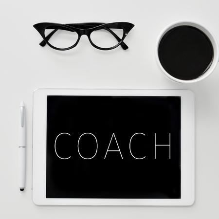 viager: Angle élevé tiré d'un bureau avec un ordinateur tablette avec le mot coach écrit en elle, une paire de lunettes femmes et une tasse de café Banque d'images
