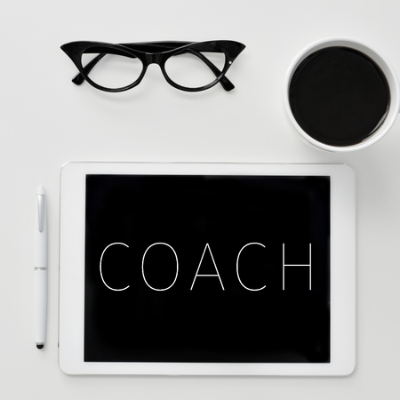 high-angle shot of a desk with a tablet computer with the word coach written in it, a pair of women eyeglasses and a cup of coffee Foto de archivo