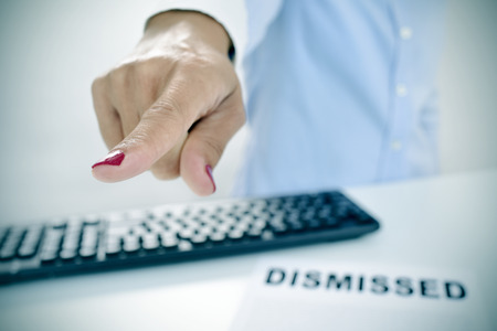 demotion: closeup of a businesswoman sitting at her desk, with a document with the text dismissed on it, pointing with her finger the way out