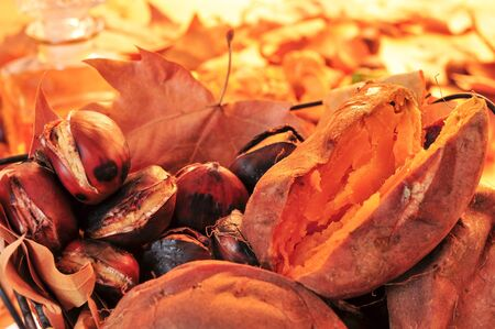 potato leaves: closeup of a rustic basket with some roasted chestnuts, some roasted sweet potatoes and autumn leaves