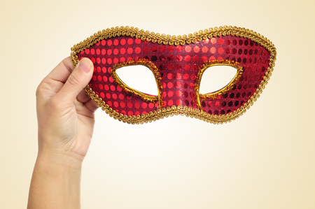 carnevale: closeup of the hand of a young woman holding a red and golden carnival mask on a beige background Stock Photo