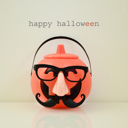 disguised: a carved pumpkin disguised with a fake nose, a moustache and black eyeglasses, and the text happy halloween