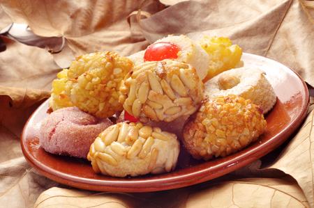 pasteles: un plato de barro con algunos panellets diferentes, pasteles típicos de Cataluña, España, se consumen en Todos los Santos, en una superficie llena de hojas secas Foto de archivo