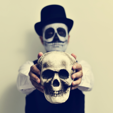 skeleton costume: a young man with calaveras makeup, wearing top hat, holds a scary skull in front of him Stock Photo