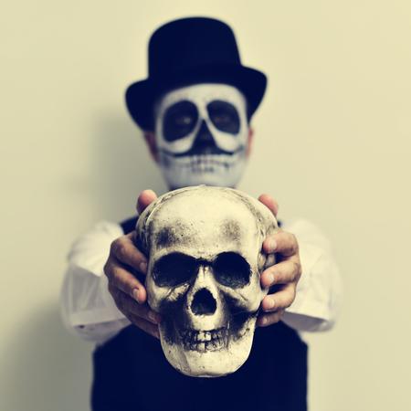 skelett mensch: ein junger Mann mit calaveras Make-up, das Tragen Hut, h�lt ein scary Sch�del vor ihm Lizenzfreie Bilder