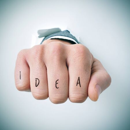 competitiveness: a young businessman breaks through a wall with his fist, and the word idea written in his knuckles Stock Photo