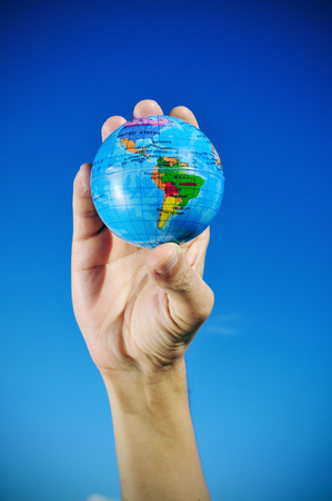 abroad: closeup of a world globe in the hand of a young man, over the blue sky, slight vignette added