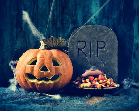 dismal: a plate with Halloween candies and an amputated finger in a dismal scene with a carved pumpkin and a gravestone with the text RIP carved in Stock Photo