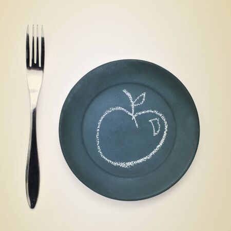 feed the poor: high-angle shot of a fork and a plate painted as a chalkboard with an apple drawn with chalk in it on a beige surface Stock Photo