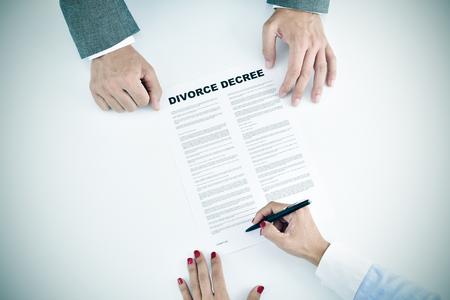 divorcio: de alto ángulo de tiro de una mujer joven que firma un documento de divorcio delante de un joven