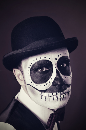 skull character: portrait of a man with calaveras makeup, wearing bow tie and bowler hat, with a vintage effect