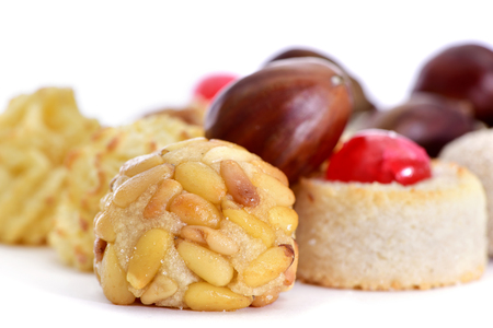 all saints day: closeup of some different panellets, typical pastries of Catalonia, Spain, eaten in All Saints Day, and some chestnuts on a white surface Stock Photo